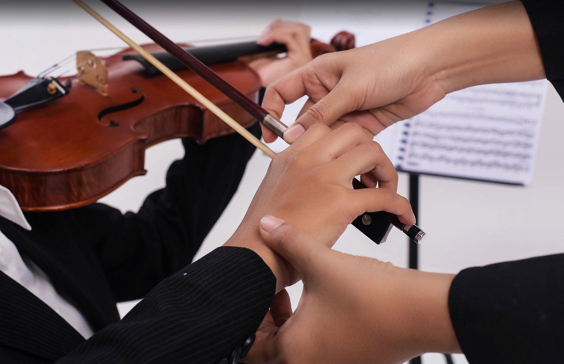 Hands instructing violin player